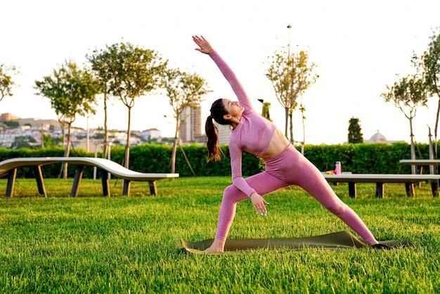 Jovem de camisa rosa e calças na grama dentro do parque verde, meditando e fazendo yoga em poses diferentes Foto gratuita