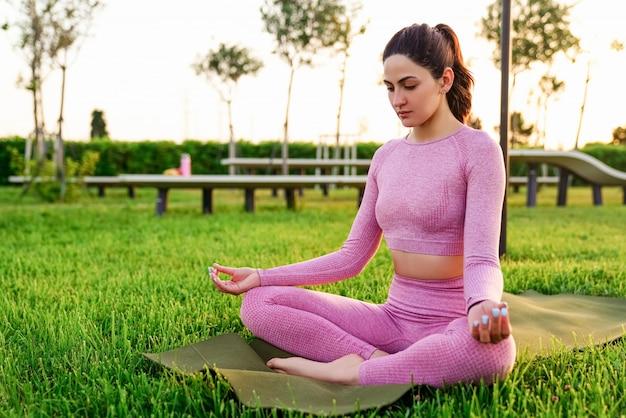 Jovem de camisa rosa e calças, sentado na grama dentro do parque, meditando e fazendo yoga Foto gratuita