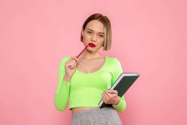 Jovem de camisa verde e calça cinza posando com caneta vermelha e caderno Foto gratuita