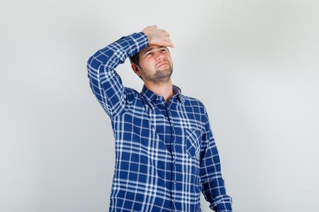Jovem de camisa xadrez sofrendo de dor de cabeça com a mão na testa Foto gratuita