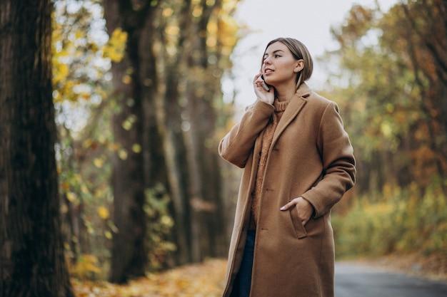 Jovem de casaco em pé na estrada em um parque de outono Foto gratuita