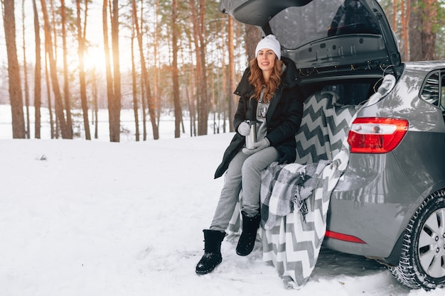 Jovem de chapéu de lã senta-se no porta-malas do carro e detém uma xícara de chá quente nas mãos dela Foto Premium