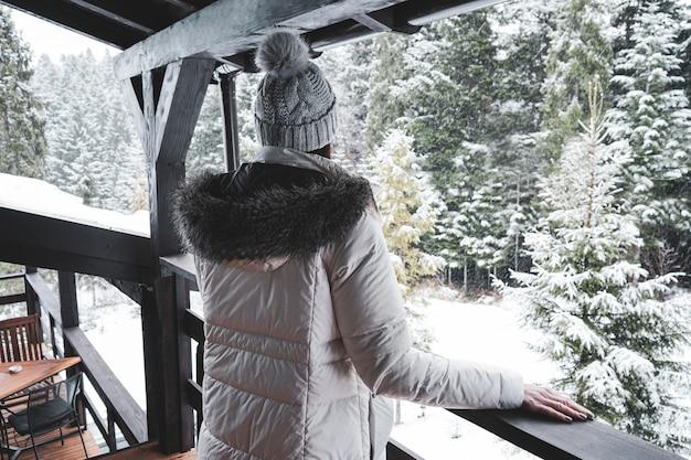 Jovem de pé em um terraço com vista para a floresta de inverno Foto Premium