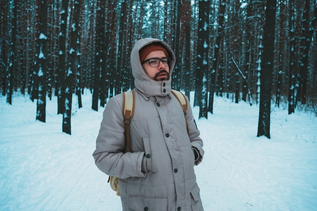 Jovem de pé na floresta de inverno nevado Foto Premium