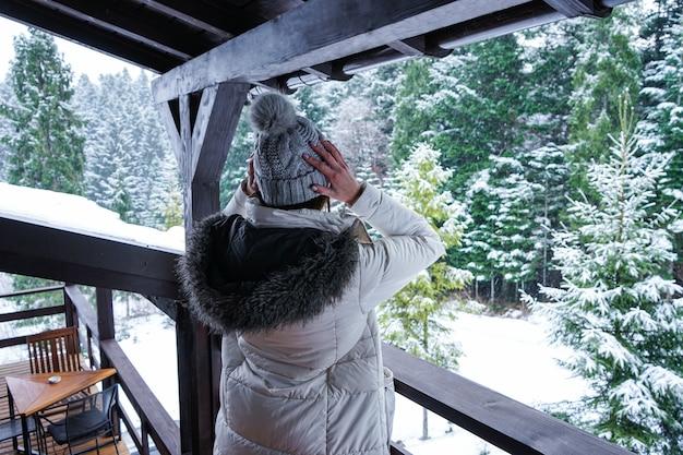 Jovem de pé no terraço em uma jaqueta branca e chapéu com vista para a floresta de inverno Foto Premium