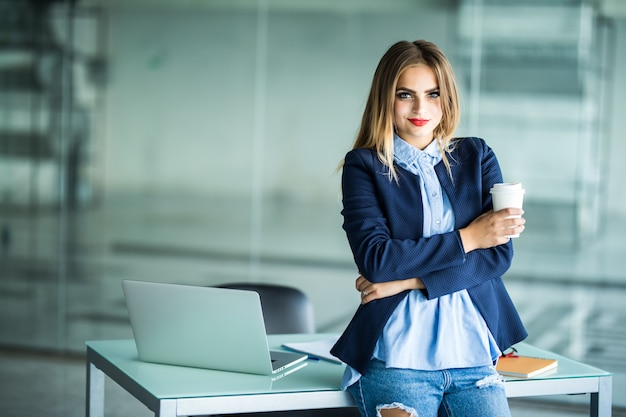 Jovem de pé perto da mesa com laptop segurando a pasta e a xícara de café. ambiente de trabalho. mulher de negócios. Foto gratuita