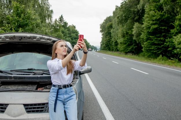 Jovem de pé perto de um carro quebrado com capô estourado, tendo problemas com seu veículo. Foto Premium