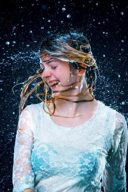 Jovem de pé sob água corrente Foto gratuita