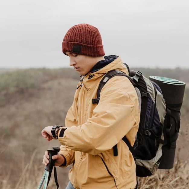 Jovem de vista lateral com equipamento de viagem Foto gratuita