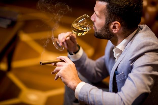 Jovem, degustação de vinho branco e fumar charuto Foto Premium