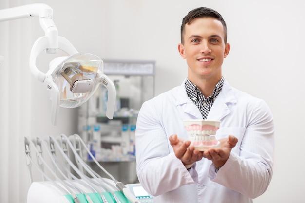 Jovem dentista masculina bonita sorrindo segurando o molde de dentadura para a câmera Foto Premium