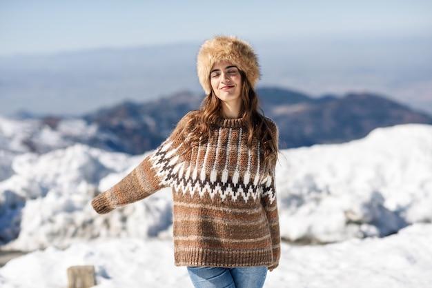 Jovem, desfrutando das montanhas nevadas no inverno Foto Premium