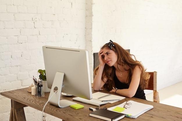 Jovem designer caucasiana se sente em pânico com o prazo final para seu trabalho, sentada no local de trabalho com papéis, um bloco de notas e olha para o monitor do computador contra a parede de tijolos brancos, parecendo intrigada Foto gratuita