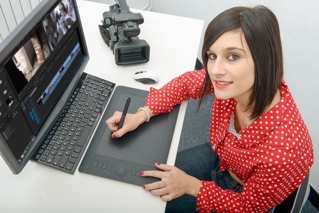 Jovem designer feminino usando mesa digitalizadora para edição de vídeo Foto Premium