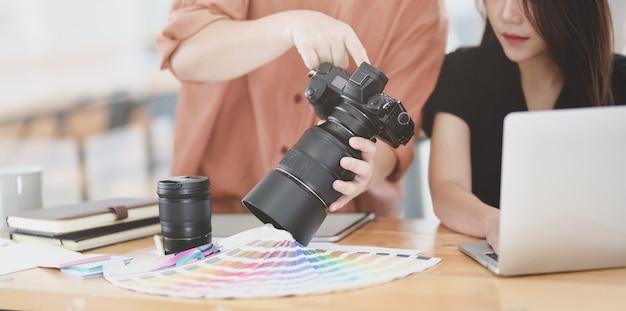 Jovem designer gráfico feminino, explicando suas idéias para seu colega de trabalho Foto Premium