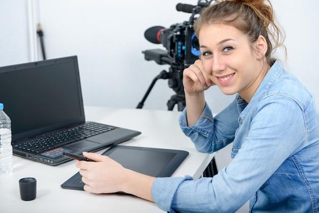 Jovem designer usando mesa digitalizadora para edição de vídeo Foto Premium