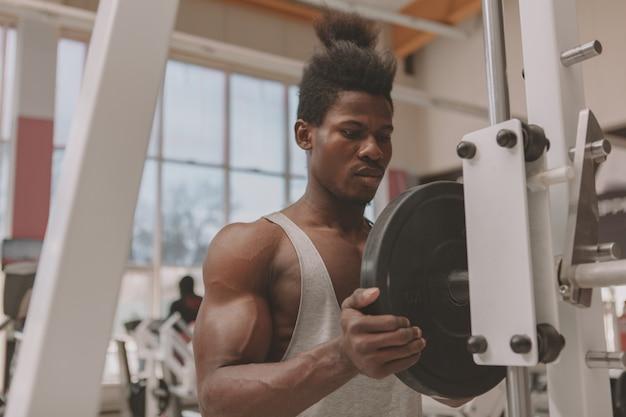 Jovem desportista malhando com barra Foto Premium