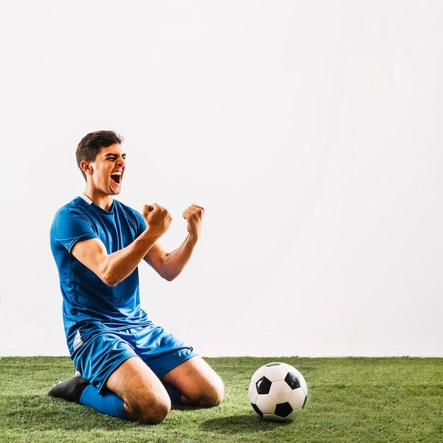 Jovem desportista, regozijando-se sobre a vitória no campo Foto gratuita