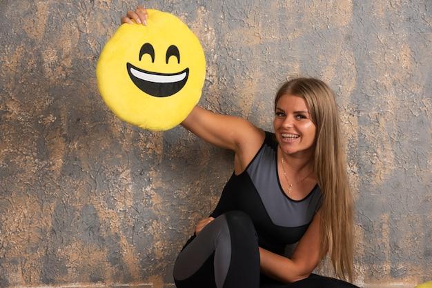 Jovem desportiva em trajes de desporto, segurando uma almofada sorridente de emoji acima. Foto gratuita