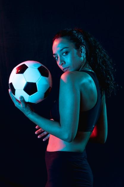 Jovem desportiva vista frontal com bola Foto gratuita