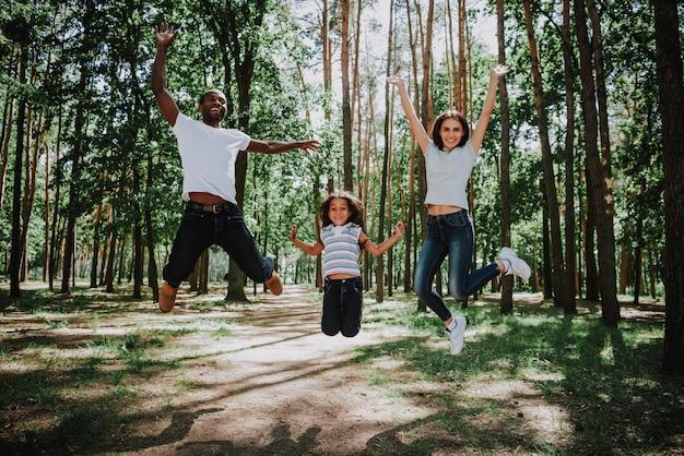Jovem desportivo família pula se diverte no parque de verão Foto Premium