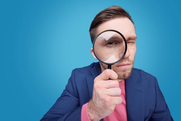 Jovem detetive sério segurando uma lupa com o olho direito enquanto está isolado Foto Premium