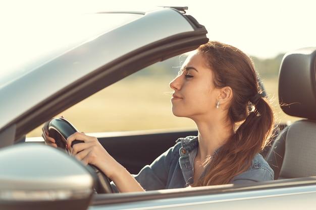 Jovem dirigindo carro cabrio, na luz do sol Foto Premium