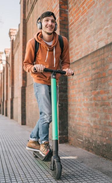 Jovem dirigindo scooter elétrico. Foto Premium