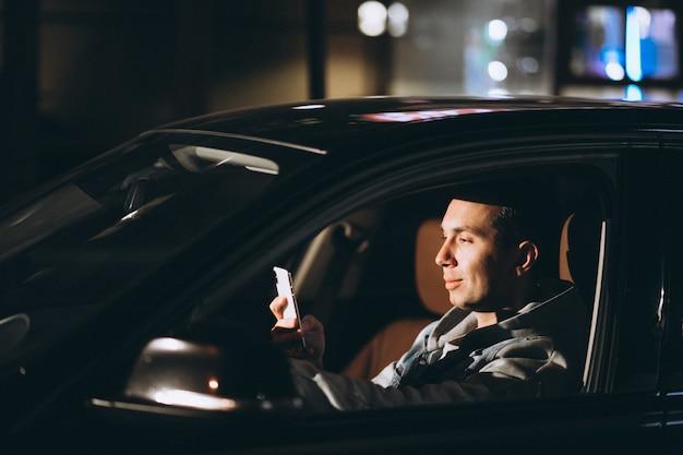 Jovem dirigindo seu carro durante a noite e falando ao telefone Foto gratuita
