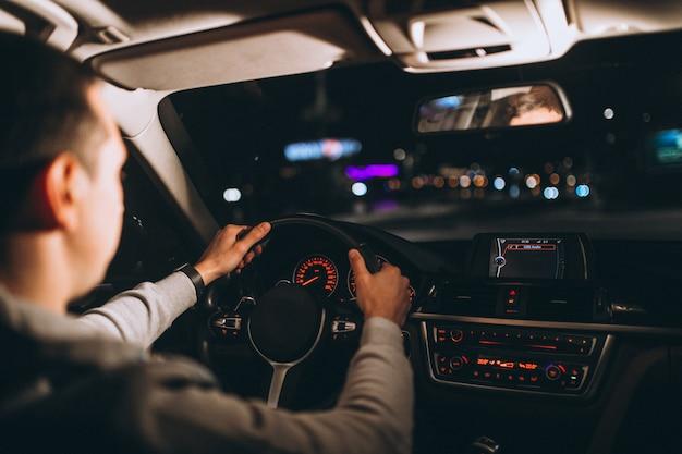 Jovem dirigindo seu carro durante a noite Foto gratuita