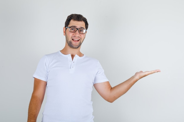 Jovem do sexo masculino com camiseta branca, óculos mostrando algo ou dando boas-vindas e parecendo alegre Foto gratuita
