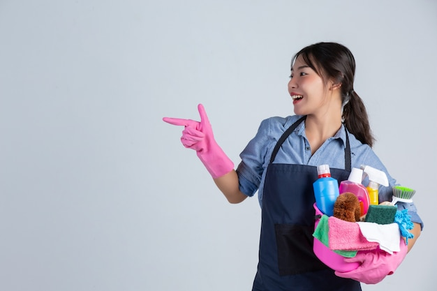 Jovem dona de casa está usando luvas amarelas durante a limpeza com o produto de limpeza na parede branca. Foto gratuita