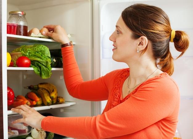 Jovem dona de casa perto de refrigerato Foto gratuita