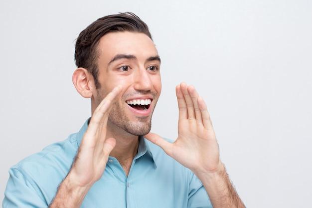 Jovem e alegre homem bonito indo gritar alto Foto gratuita
