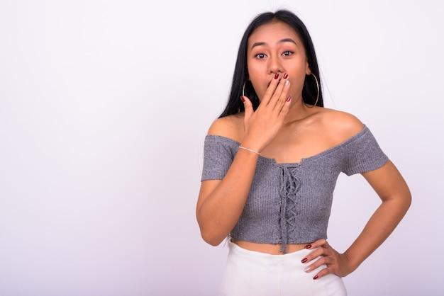 Jovem e bela mulher asiática contra uma parede branca Foto Premium