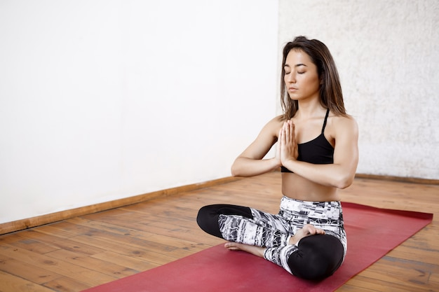Jovem e bela mulher atlética praticando ioga interior no tapete vermelho Foto gratuita