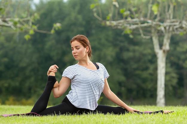 Jovem e bela mulher fazendo exercícios de ioga em um parque verde Foto gratuita