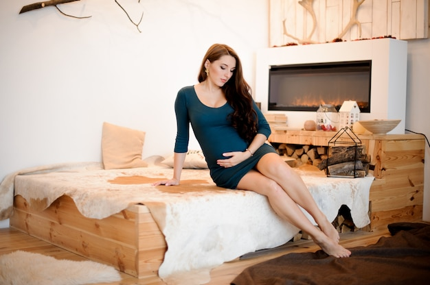 Jovem e bela mulher grávida de cabelos compridos, sentado perto da lareira Foto Premium
