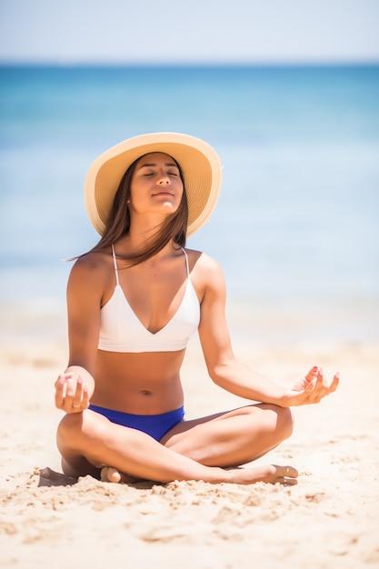 Jovem e bela mulher meditando na praia perto do mar Foto gratuita