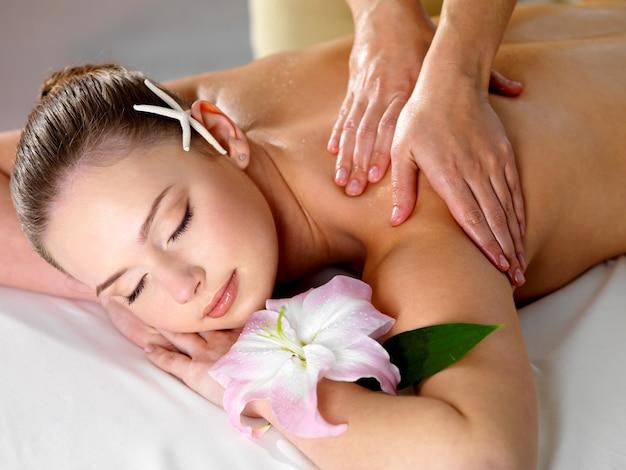Jovem e bela mulher recebendo massagem relaxante nos ombros em salão de beleza - dentro de casa Foto gratuita