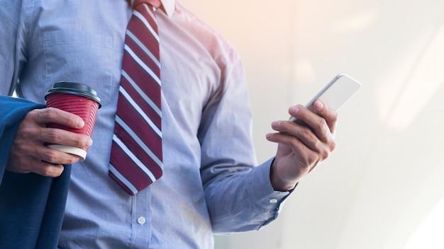 Jovem e bem sucedido empresário está lendo uma mensagem em seu smartphone. Foto gratuita