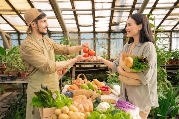 Jovem e bonito fazendeiro barbudo de avental e boné vendendo vegetais maduros para uma mulher asiática em uma mercearia Foto Premium