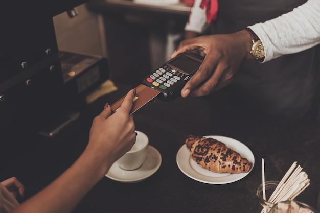 Jovem é calculado o café por cartão de crédito Foto Premium