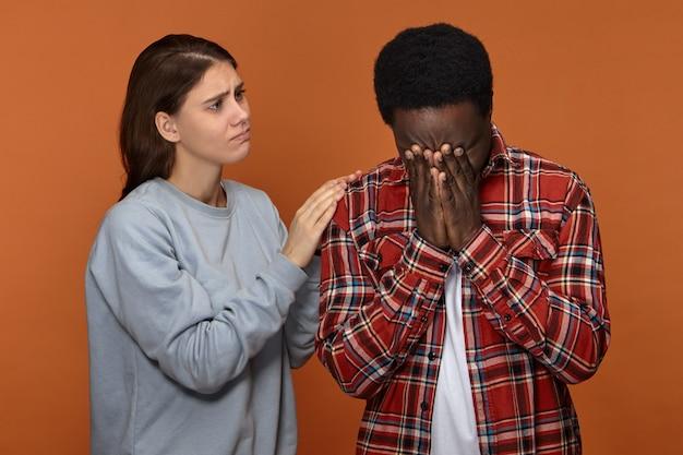 Jovem e compassiva linda esposa branca confortando e consolando o infeliz marido negro que está chorando por causa de sérios problemas no trabalho. mulher europeia carinhosa apoiando o namorado africano Foto gratuita