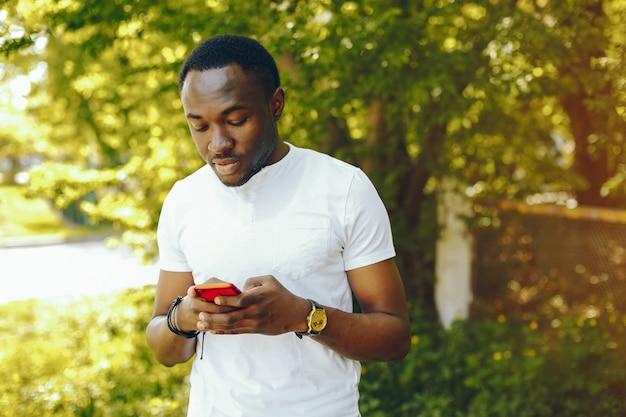 Jovem e elegante menino de pele escura em uma camiseta branca fica em um parque de verão ensolarado Foto gratuita