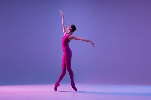 Jovem e graciosa dançarina de balé isolada no fundo roxo do estúdio em luz de néon Foto gratuita