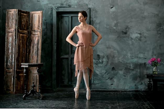 Jovem e incrivelmente linda bailarina está posando e dançando em um estúdio preto Foto gratuita