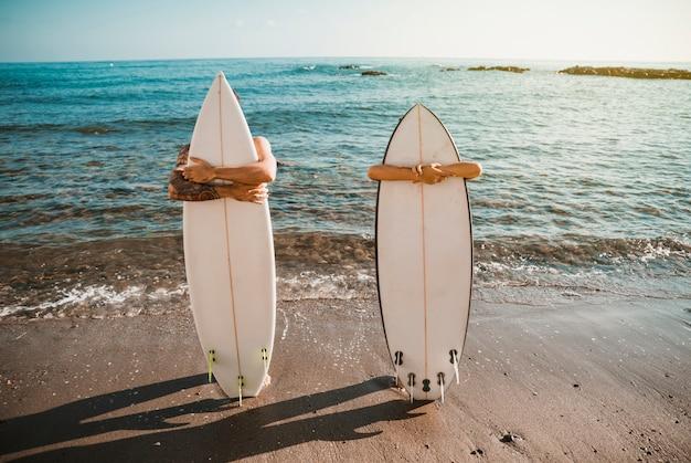 Jovem e mulher com pranchas de surf na costa perto da água Foto gratuita