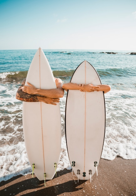 Jovem e mulher com pranchas de surf na costa perto do mar Foto gratuita