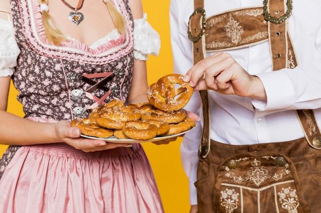 Jovem e mulher com pretzels da baviera Foto gratuita